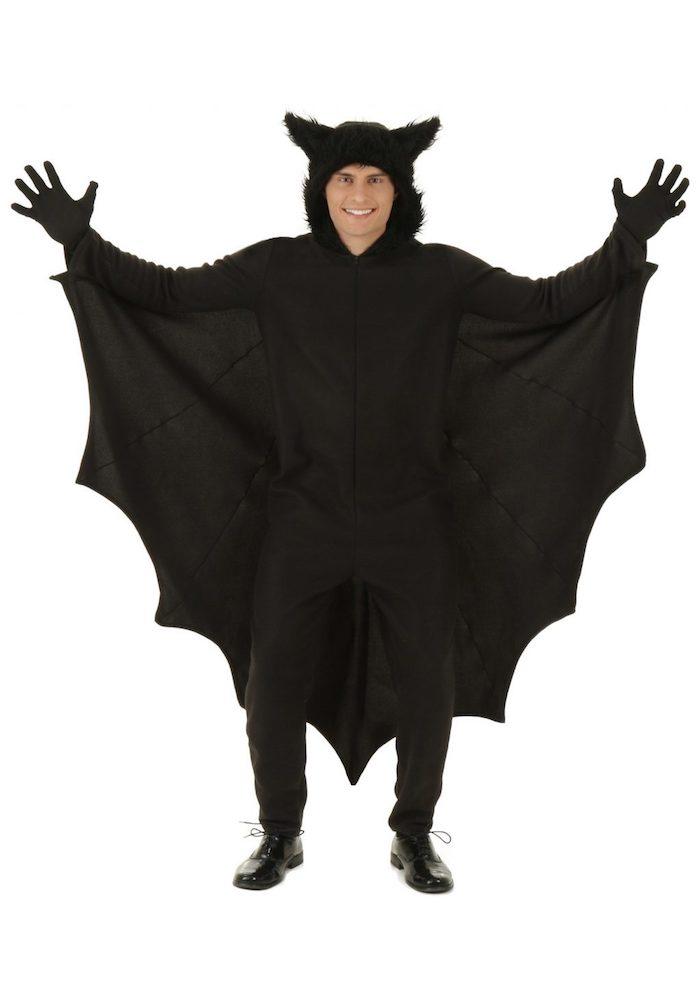 ein junger mann mit einem großen schwarzen fledermaus kostüm mit großen schwarzen ohren und mit schwarzen flügeln, eine fledermaus häkeln