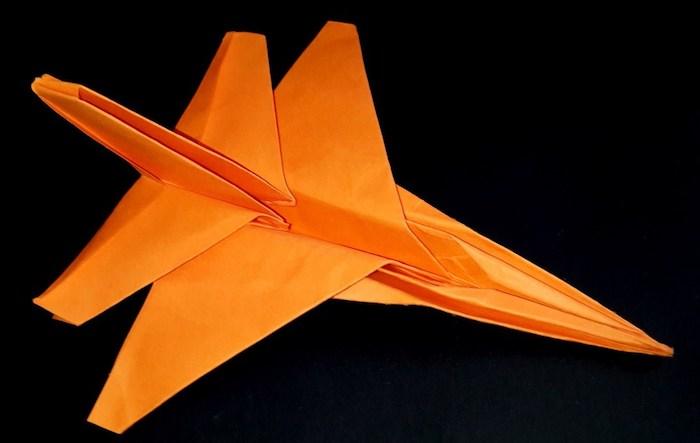 ein oranger jagdflugzeug aus papier, ein kleiner oranger papierflieger, bester papierflieger der welt