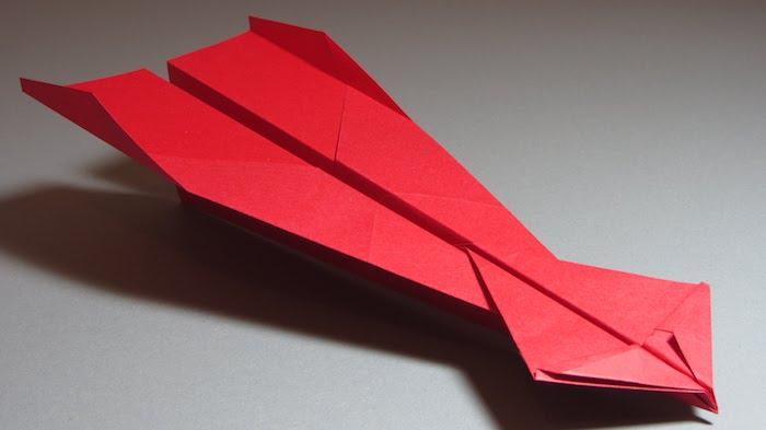 ein grauer tisch und ein roter großer papierflieger, bester papierflieger der welt, bastelideen mit papier