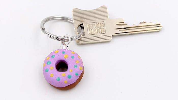 kleiner schlüsselanhänger mit einem kleinen pinken donut aus einer fimo knete, schlüssel aus metall, fimo ideen