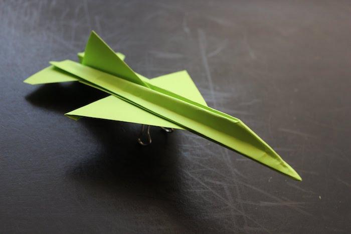 ein tisch und ein kleiner grüner papierflieger, basteln mit papier, ein grüner jagdflugzeig aus papier