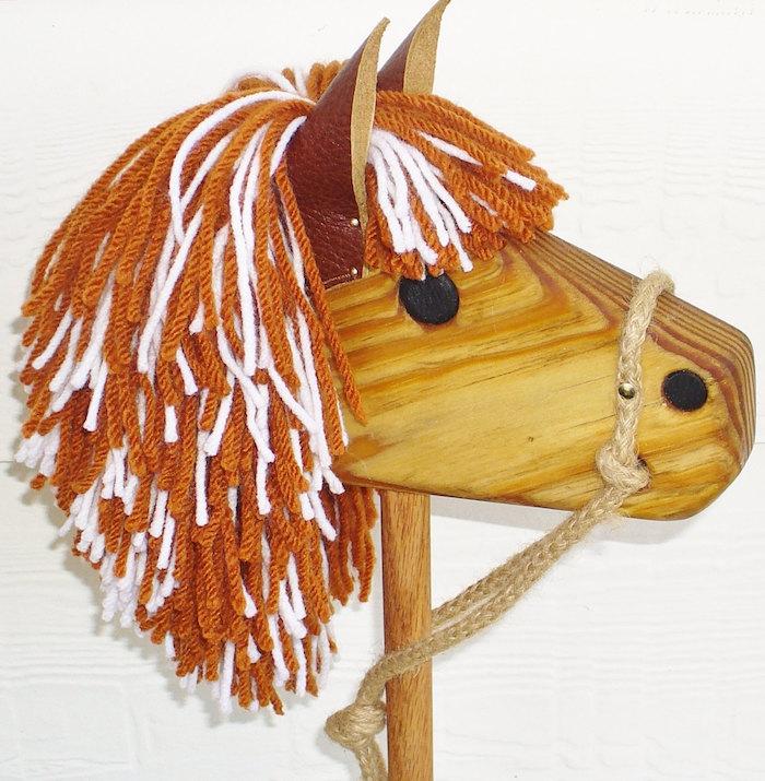 ein pferd aus holz und mit schwarzen augen und einer braunen mähn, ein selbstgebasteltes steckenpferd, die schönsten spiele der welt