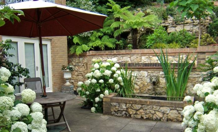 Wasserhahn in der Form von Löwen, Kübelpflanze Terrasse voller Sonne, weiße Blumen