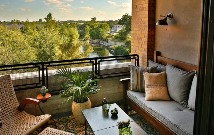 Rattan Liegestuhl, ein Sofa mit vielen Kissen, ein Blumentopf, Terrasse dekorieren