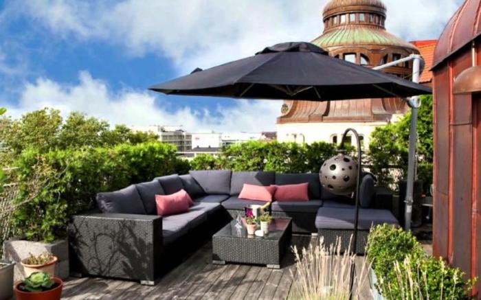 schwarzer Sonnenschirm, ein kleines Tischlein, schwarze Terrassenmöbel, Terrassen dekorieren