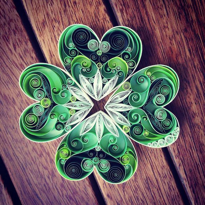 ein großer grüner quilling klee mit vier grünen blättern aus grünen und weißen langen papierstreifen, frühling basteln