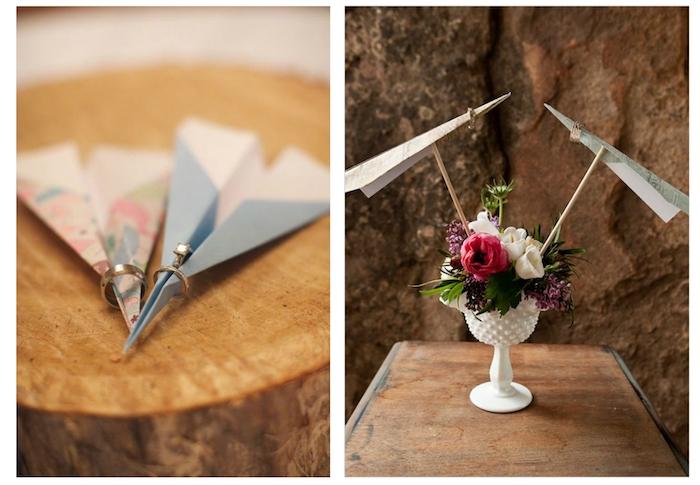 ein pinker papierflieger mit einem ehering, rote und weiße rosen und grünen pflanzen, ein blauer papierflieger mit einem ehering