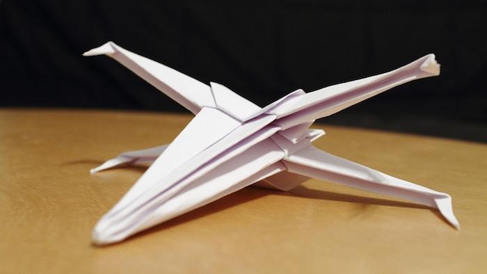 bester papierflieger der welt, ein tisch aus holz und ein kleiner weißer papierflieger, papierflieger falten a4