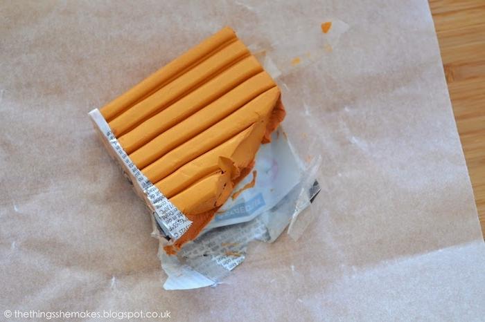 eine orange fimo knete und ein tisch aus holz, fimo ideen anleitung, fimo backen