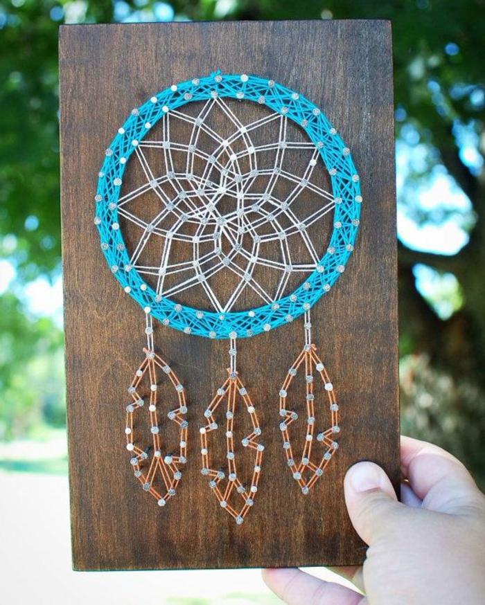 kreative Fadenbilder Motive, ein blauer Traumfänger mit drei orangen Federn