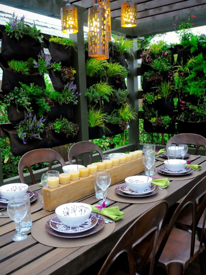 hängende Blumentöpfe mit Blumen, eine Reihe von Kerzen auf dem Tisch, Blumenkübel bepflanzen