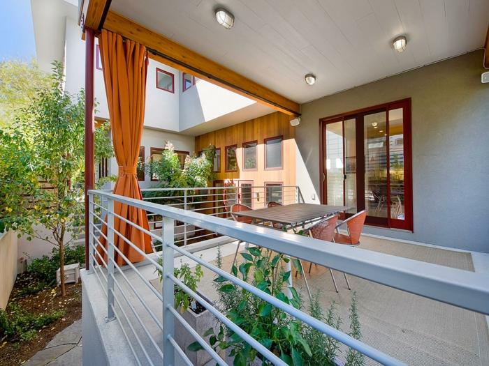 ein Teppich als Terrassenbelag, oranger Vorhang, vier orange Stühle, Tisch aus Holz, Terrasse dekorieren