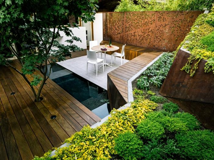 Terrasse mit einem Wasserspiel, Gartenmöbel wie auf eine Insel, ausgefallener Sichtschutz
