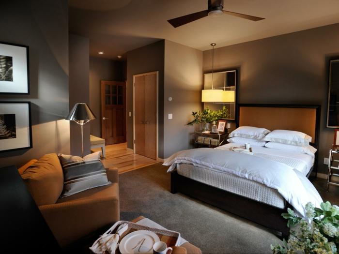 moderne Zimmer mit einem großen Bett und Leseecke, grauer Teppich, Pflanzen als Dekoration