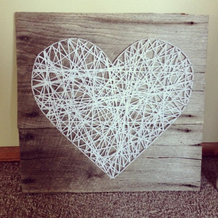 ein weißes Herz aus Fäden, braunes Brettchen, eine romantische Deko am Valentinstag,
