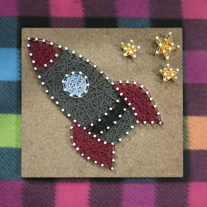 eine Rakette in roter und grauer Farbe mit einem blauen Bullauge, kleine gelbe Sterne, String Art Bild