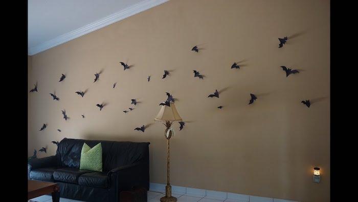 eine wand mit einer dekoration mit vielen kleinen schwarzen fliegenden fledermäusen aus papier, ein schwarzes sofa mit grünen kissen und eune lampe, kleine fledermaus zeichnen