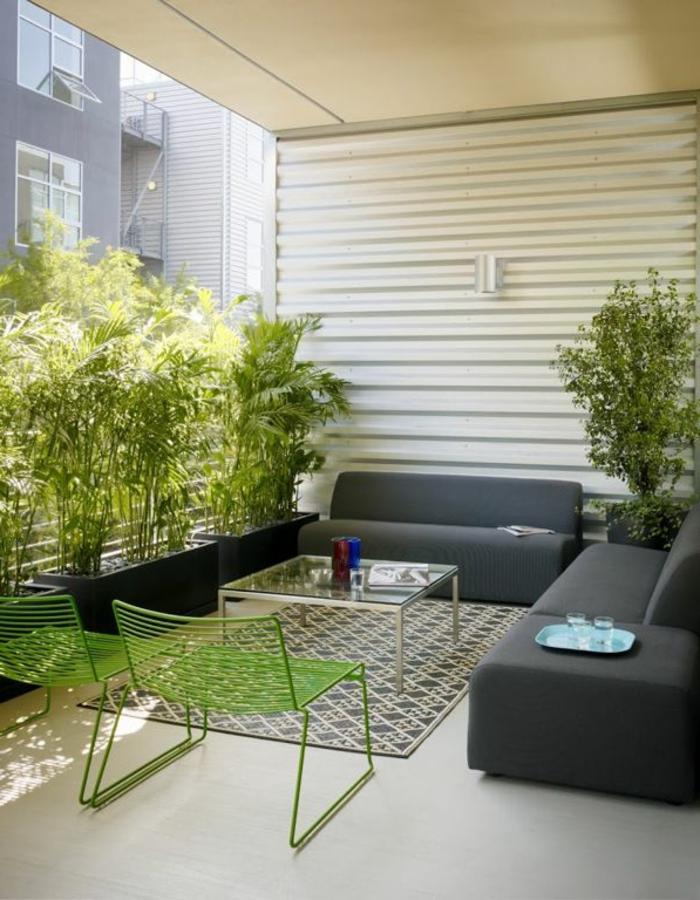 eine Terrasse mit Terrassenpflanzen in schwarzen Pflanzenkübel, graue Loungemöbel