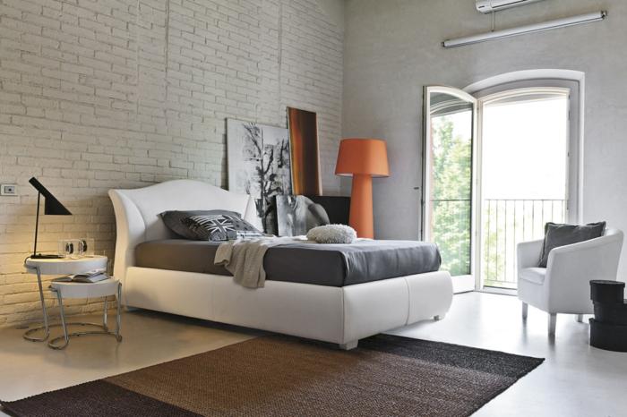 eine ausgefallene Schlafzimmer Deko mit schwarz weißes Bild, graues Bett, ein bunter Teppich