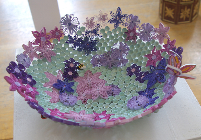 eine quilling schüssek aus violetten, pinken und blauen papierstreifen und mit einem pinken schmetterling aus papier, basteln zu ostern