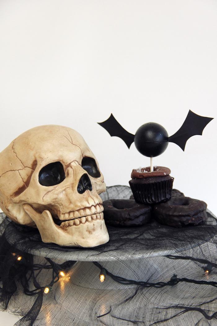 eine weiße wand und ein totenkopf mit schwarzen augen, eine kleine schwarze fledermaus aus einem kleinen schwarzen ball und mit zwei schwarzen flügeln aus papier, kuchen mit einer fledermaus, fledermaus basteln aus papier