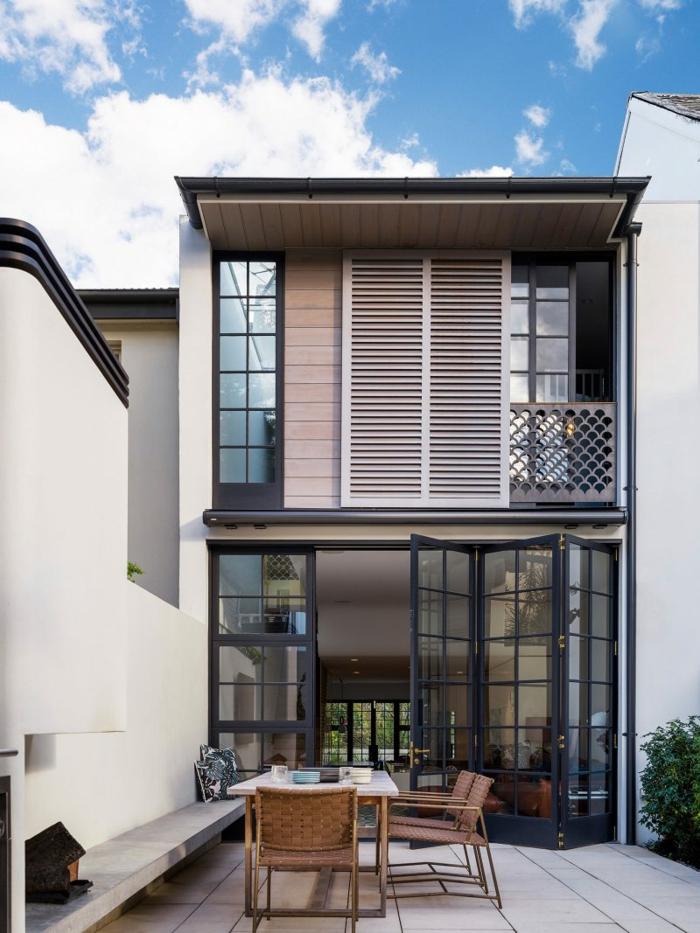 ein modernes Haus, moderne Terrasse, bequeme Sitzplätze und eine Hecke