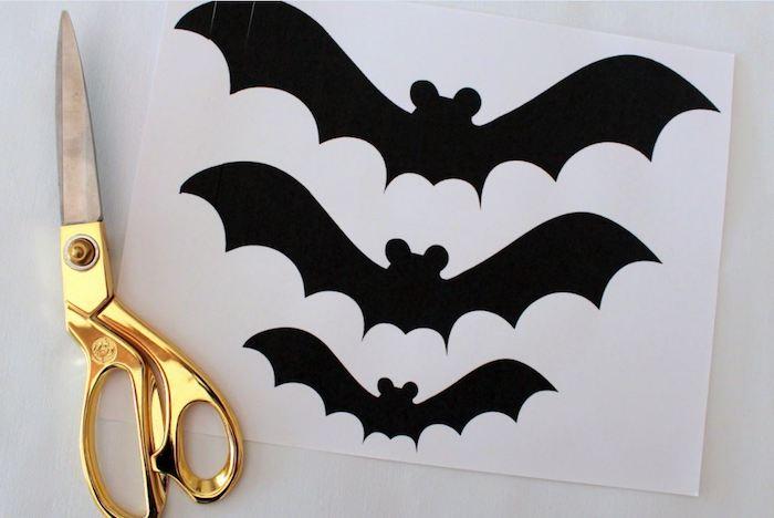 ein blatt papier mit drei kleinen schwarzen fledrmäusen mit schwarzen flügeln und mit schwarzen ohren, eine grpße goldene schere, eine fledermaus selber bastreln
