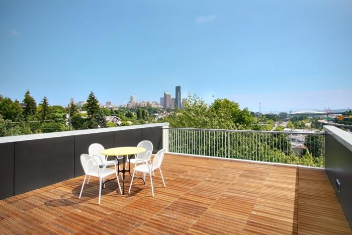 eine geräumige Dachterrasse, moderne Terrasse mit Fliesen, vier weiße Stühle und Tisch