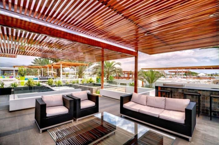 Terrassenüberdachung aus Bambus, modene Terrasse mit zwei Sessel und ein Sofa, Tisch mit gläsernem Oberteil