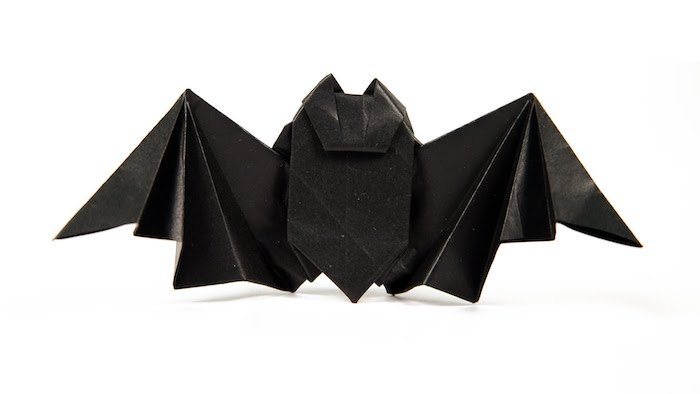 eine kleine diy origami fledermaus aus papier selber basteln, eine fledemaus mit schwarzen flügeln und schwarzen ohren aus papier