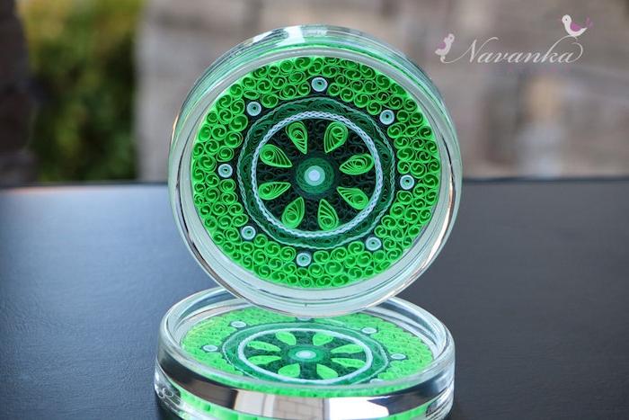 ein tisch und kleine grüne quilling figuren mit vielen langen grünen und schwarzen papierstreifen
