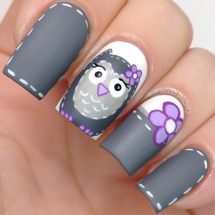 eine hand mit vier fingern mit einem grauen nagellack mit einer kleinen eule mit schwarzen augen und mit kleinen violetten blumen, eine kleine eule malen