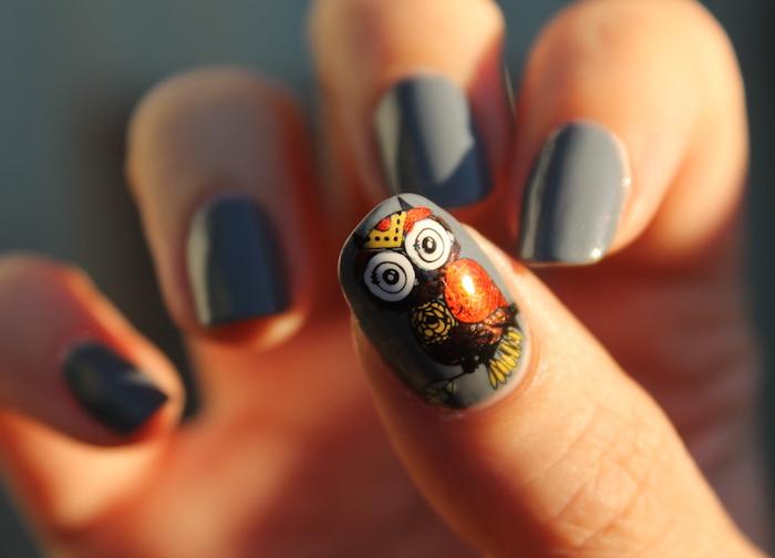 eine eule malen, hand mit fingern mit einem grauen nagellack mit einer kleinen schwarzen eule mit orangen federn, eulen basteln vorlage