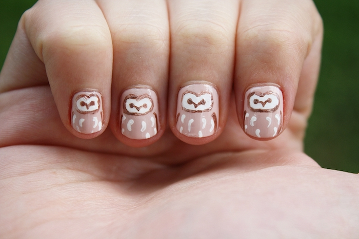 eule malen, eine hand mit einem nagellack mit vier kleinen weißen eulen