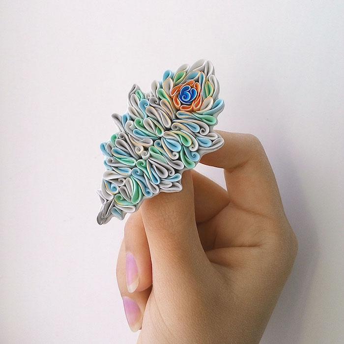 eine weiße wand und eine hand mit einem pinken nagellach mit einer kleinen fimo figur, fimo knete ideen