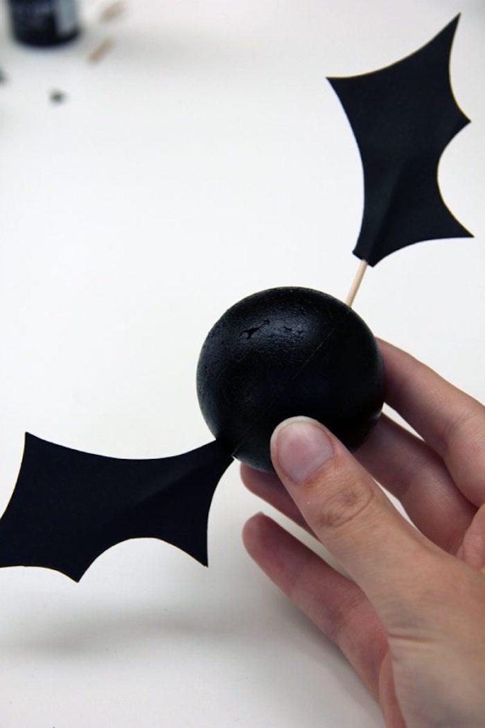 eine hand mitb einem kleinen schwarzen ball, eine kleine schwarze fledermaus mit flügeln aus papier und mit einem kleinen gelben zahnstocher