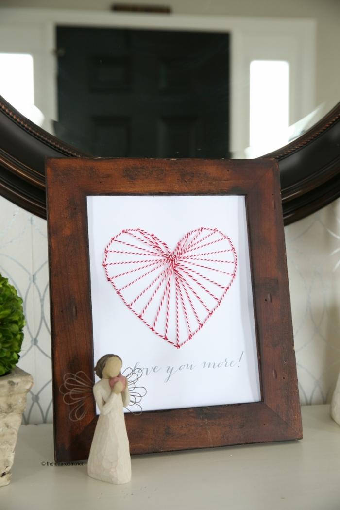 eine romantische Deko mit Nagelbilder von Herz mit roten und weißen Fäden