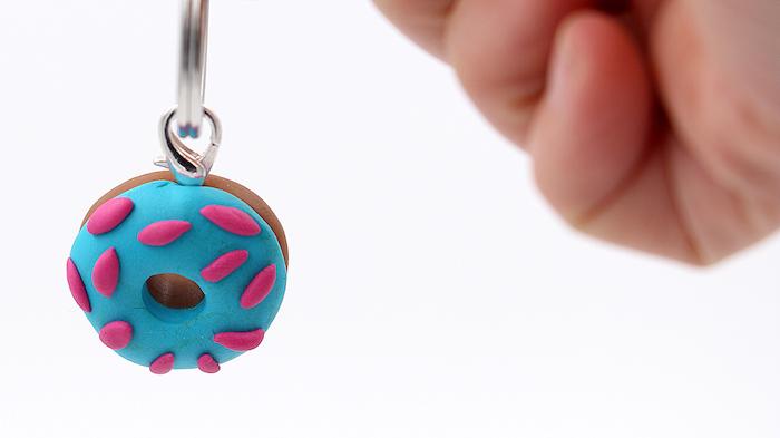eine hand mit einer kleinen fimo figur mit einem kleinen blauen donut aus einer pinken und einer blauen fimo knete, kette mit fimo figuren, idee für fimo schmuck, bdastelideen für erwachsene