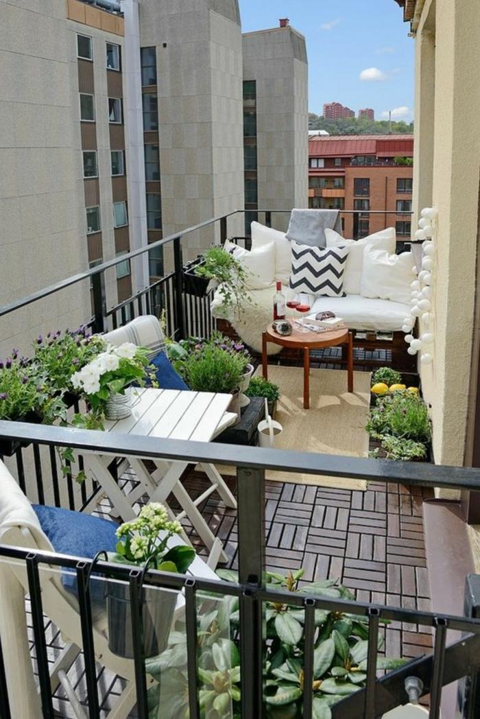 eine winzige Terrasse mit weißem Sofa, zwei blaue Stühle und weißes Tischlein, Terrasse planen