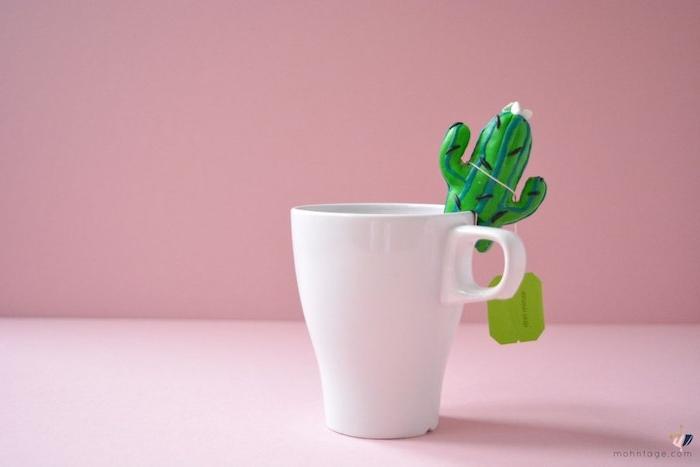eine tasse mit tee und einem selbstgebastelten grünen kaktus aus einer grünen fimo knete und eine pinke wand