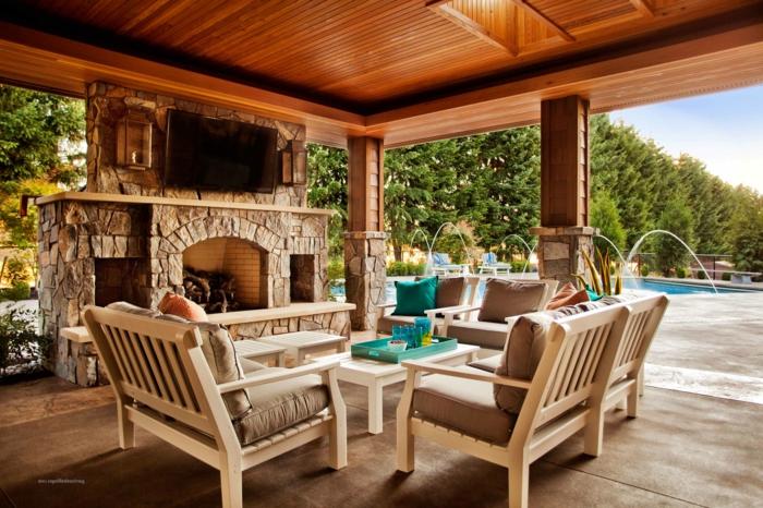 Pergola aus Holz, ein Kamin aus Steine, bequeme Loungemöbel, prächtig Terrasse gestalten