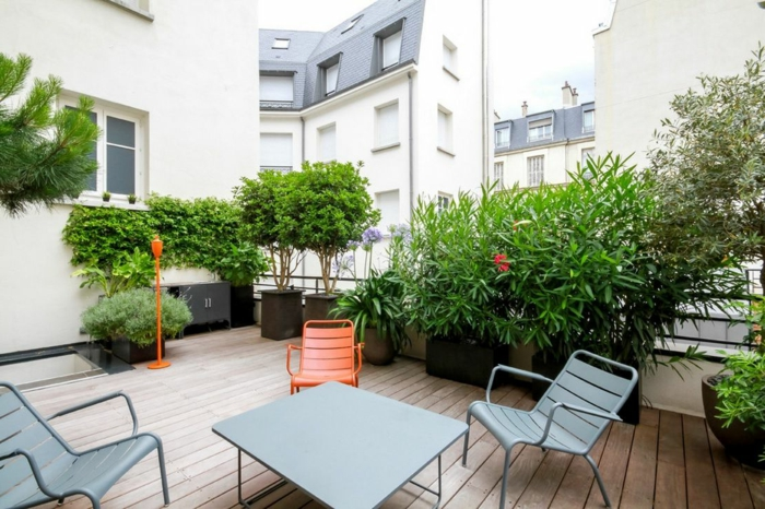 zweite Position, die Ecke vom Haus, bunte Stühle, schwarze Pflanzkübel, Terrassenbepflanzung