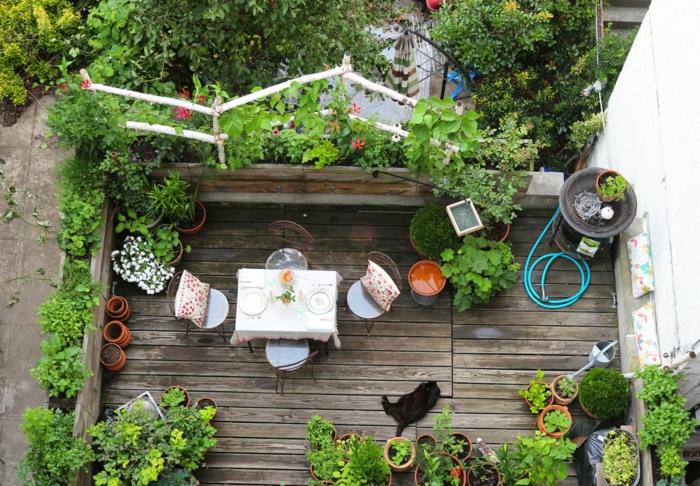 viele Terrassenpflanzen, ein kleiner Tischlein mit vier Stühlen, braune Terrassendiele