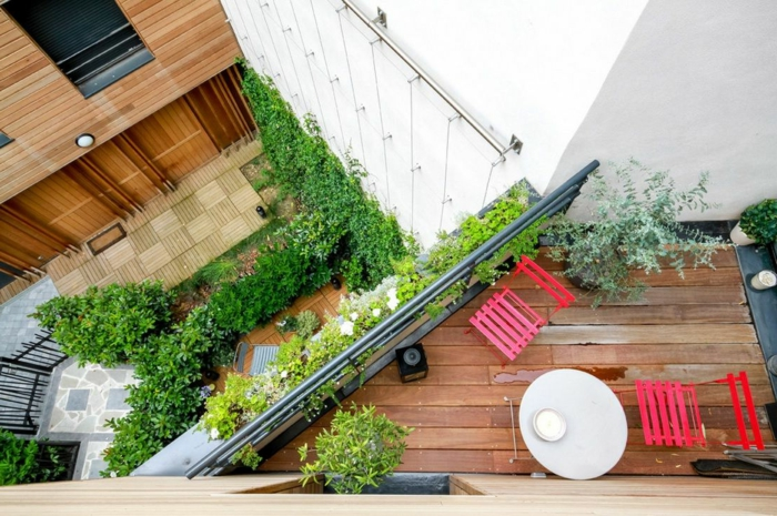 zwei Terrassen mit Terrassenpflanzen von oben, eine mit roten Stühlen, die andere mit blauen Stühlen