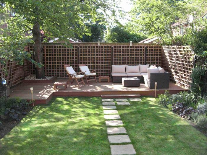 ein Baum in der Ecke, weiße Loungemöbel, ein Sichtschutz aus Holz, Terrassenpflanzen