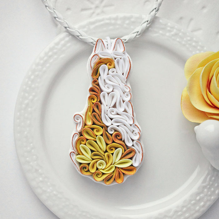 eine katze aus fimo knete, eine fimo kette mit einer fimo fugur, tischdekoration mit einem weißen teller und einer gelben rose