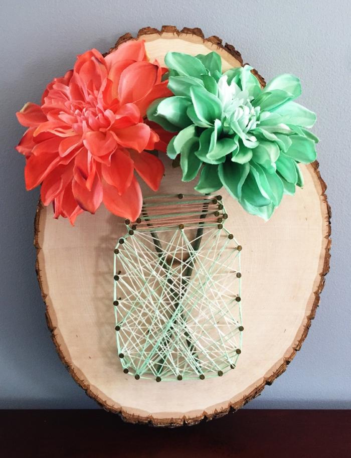 eine echte Fadenkunst, zwei Blumen in roter und grüner Farbe in einer Vase aus Fäden