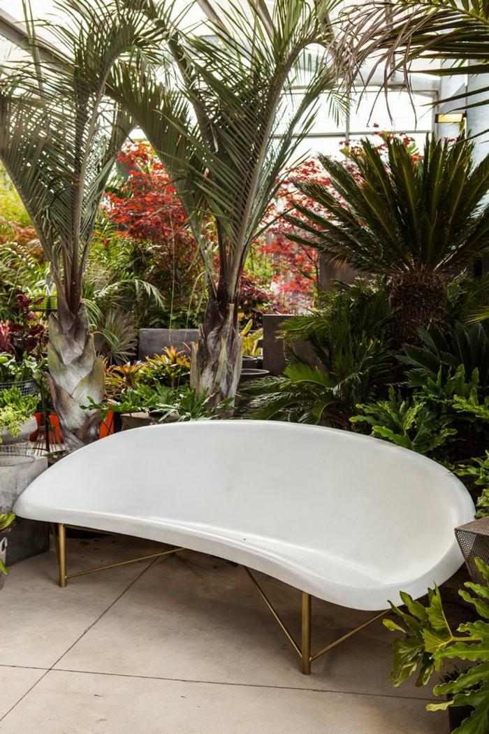 Palmen als Terrassenpflanzen, weiße ausgefallene Bank aus Plastik, große Terrassendiele