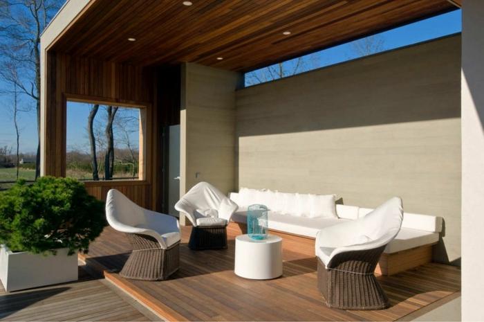 drei bequeme Rattan Stühle, eine Bank mit weißer Decke und Kissen, Terrasse dekorieren