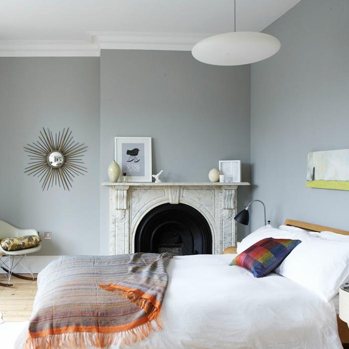 mit Kamin und Spiegel wie die Sonne das Schlafzimmer dekorieren, buntes Kissen auf das Bett